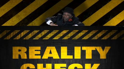A man attempts to push down a graphic that says Reality Check on it